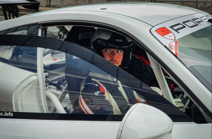 A driver sat in a porsche car having driver coaching on a track day
