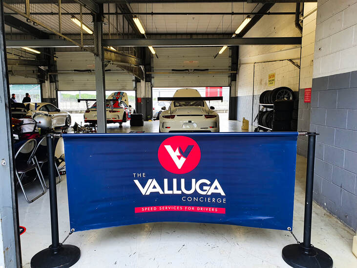 Running a driver track day with Valluga signage in front of a pit lane garage with Porsche cars in